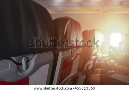 Blurred background of interior aircraft , flight attendant helping passenger to put luggage cabin compartment, Soft focus. - stock photo