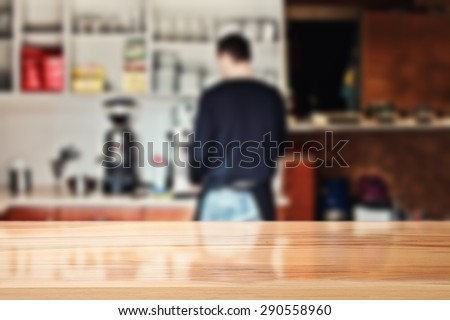 blurred background of interior in bar with barista and top of wood space  - stock photo