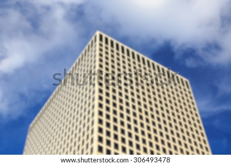 Blurred background of monolithic bright skyscraper rises before the camera. - stock photo
