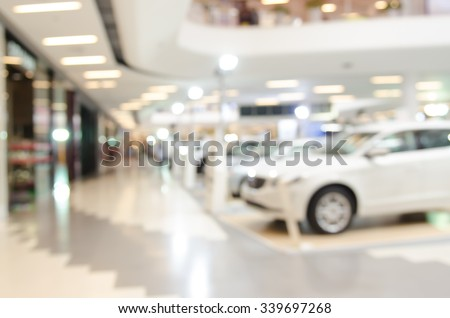 Blurred background of new cars displayed in showroom. - stock photo