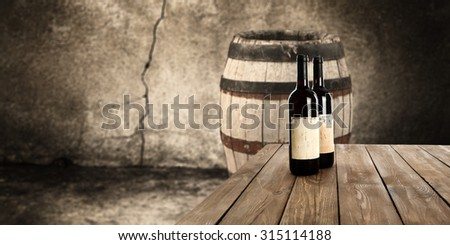 blurred background of old barrel and table and wine bottles  - stock photo