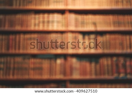 Blurred background of old books on shelves in library. Vintage books, retro style. - stock photo