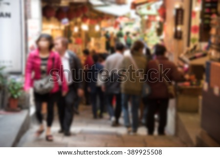 Blurred background of  people shopping at flea market on the road.