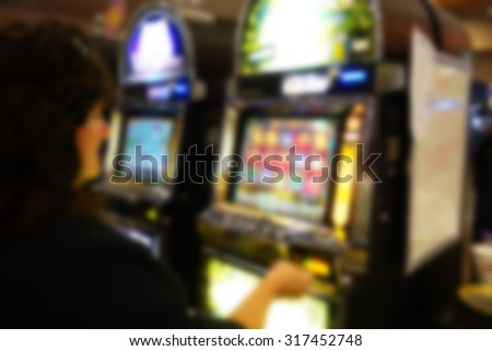 blurred background of person playing slot machines in casino - stock photo