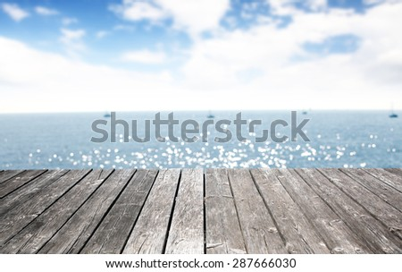 blurred background of sea and sky with gray pier  - stock photo
