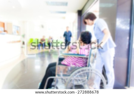 blurred background of senior female  patient in wheelchair sitting in hospital with nurse  - stock photo