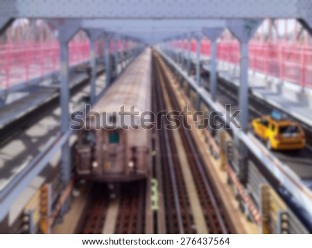 Blurred background of subway train and yellow cab pass each other on the Williamsburg Bridge in New York, NY, USA. - stock photo