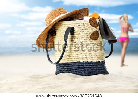 blurred background of summer coast and woman in pink bikini with summer bag  - stock photo