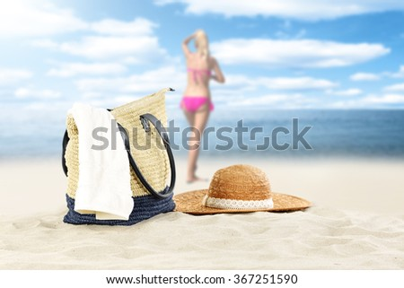 blurred background of summer coast and woman in pink bikini with white towel bag and hat  - stock photo