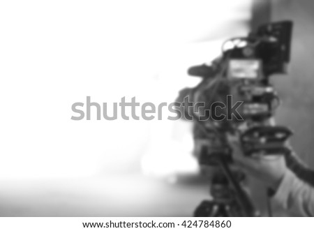 blurred background of videographer working wiht Professional equipment video camera  shooting movie cinema video for broadcast TV television - stock photo
