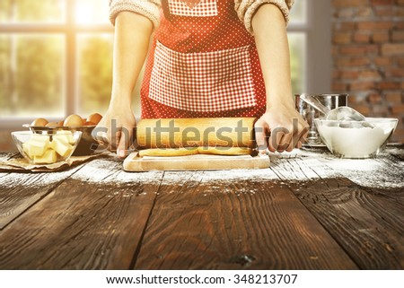 blurred background of window in kitchen and wooden table of flour and cake