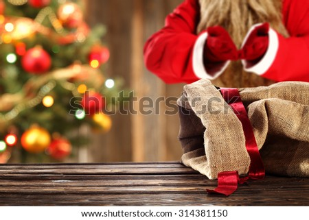 blurred background of xmas tree in home and red santa claus with red ribbon and sack  - stock photo