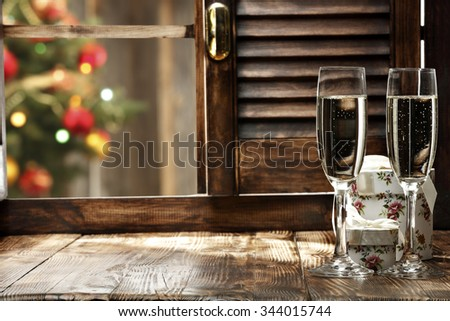 blurred background of xmas tree lights and window of glasses of champagne and window sill  - stock photo