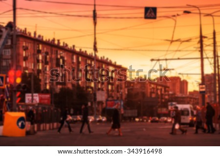 Blurred background: street with road, cars, pedestrian, crosswalk, traffic lights, signs etc on the sunset in Moscow, Russia. Image with toning - stock photo