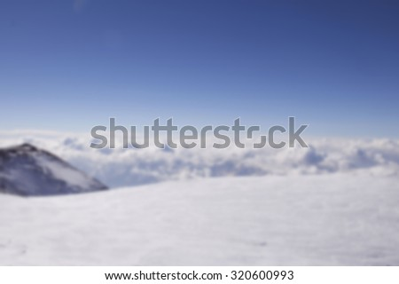 blurred background with snowy mountains. Beautiful winter panorama with snow covered trees blurred and filtered