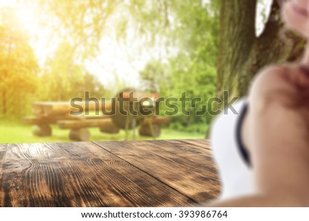 blurred background with young woman and deck top place and free space for you  - stock photo
