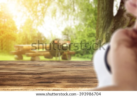 blurred background with young woman and free space for you and wooden table place  - stock photo