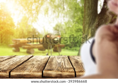 blurred background with young woman and grill time and old table  - stock photo