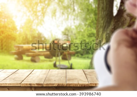 blurred background with young woman and yellow wooden old table place  - stock photo