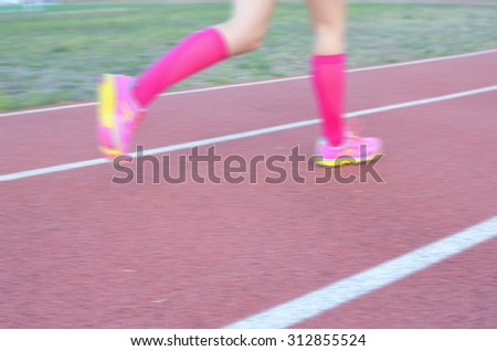 Blurred background: woman runner's legs running on track, sport and fitness concept