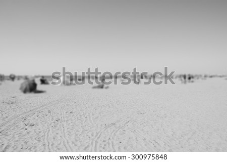 Blurred beach photo with selective focus on the sand at foreground. People relaxing on beach. Vacation background (Trouville-sur-Mer, Normandy, France) Aged photo. Black and white. - stock photo