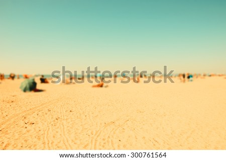 Blurred beach photo with selective focus on the sand at foreground. People relaxing on beach. Vivid sunlight. Vacation background (Trouville-sur-Mer, Normandy, France) Retro aged photo.  - stock photo
