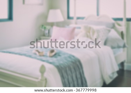 blurred bedroom with pillows and doll on white bed for background