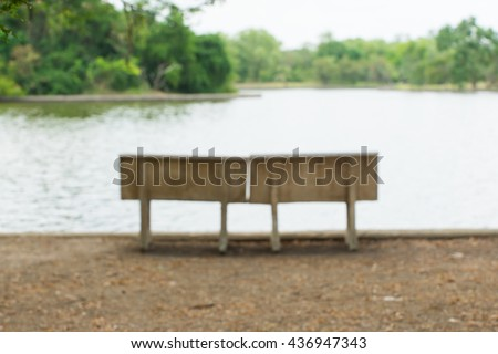 Blurred benches beside the lake in the park.
