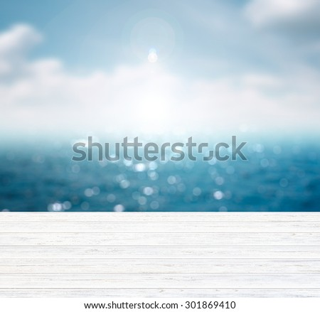 Blurred blue background of sea and sky with free space on wooden table. - stock photo