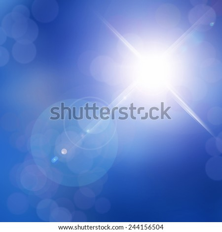 Blurred blue bokeh background with lens flare sparkle