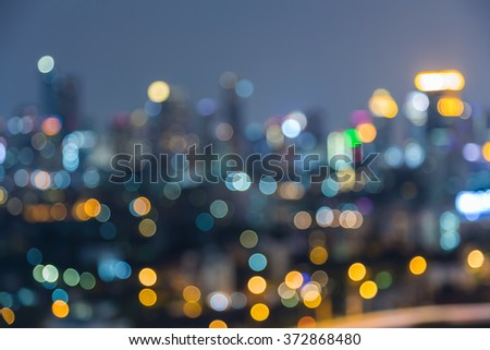 Blurred bokeh business district lights at night - stock photo