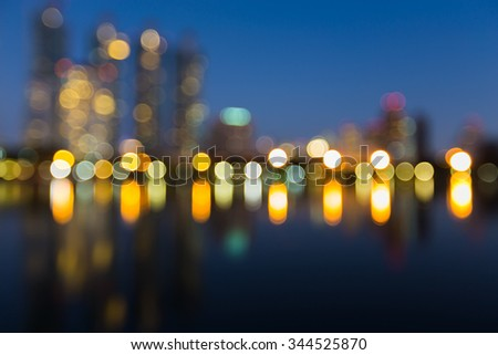 Blurred bokeh lights city downtown background with water reflection - stock photo