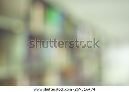 Blurred books on the shelf and the light from windows in public library. Blurred effect. Background for your pictures - stock photo