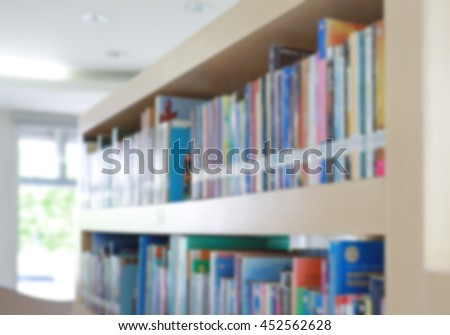 Blurred bookshelf in library, abstract blur defocused background - stock photo