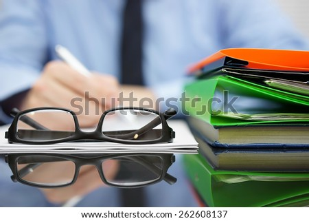 Blurred Businessman is writing document, focus on glasses and folders