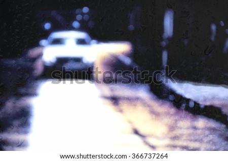 Blurred car behind wet glass on the road at night - stock photo
