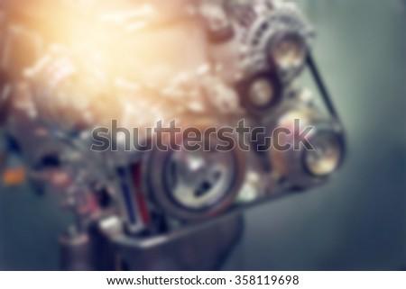Blurred car engine part on dark background - stock photo