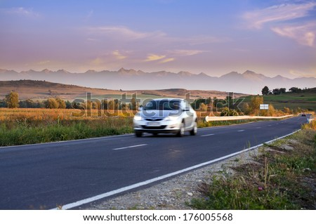 Blurred car traveling on road with beautiful mountain ridge landscape in Transylvania Romania - stock photo