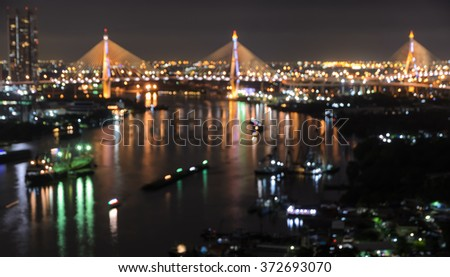 Blurred city skyline bokeh lights illuminated at night with reflection on river