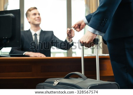 Blurred close up photo of receptionist and client in expensive hotel. Customer with suitcase giving his credit card to receptionist - stock photo