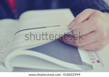Blurred, closeup image of a man reading, one hand holding the page of a computer text book. Toned image. Reading background. - stock photo