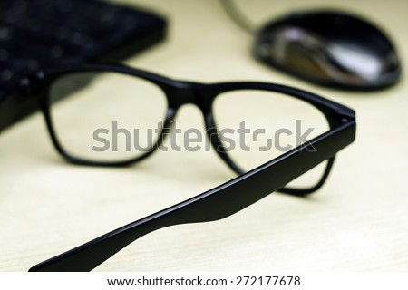 blurred closeup of glasses , keyboard and mouse on table with a very shallow depth of field with copy space for text
