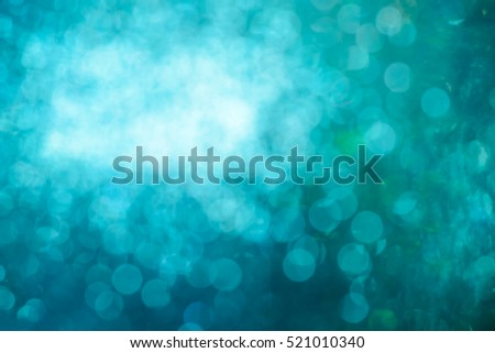blurred closeup of turquoise glittering christmas decoration ornaments, abstract background