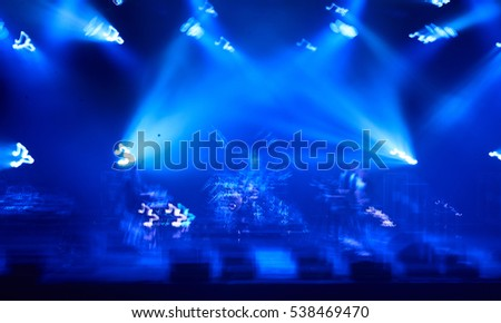 Blurred concept of night life. Crowd in front of stage with blue concert lights