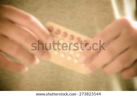 Blurred control pill on hand young girl with vintage style - stock photo