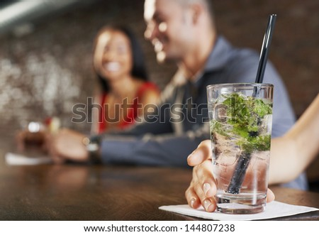 Blurred couple sitting at bar with cocktail glass in foreground