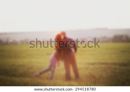 Blurred couple standing in the field at the sunset - stock photo