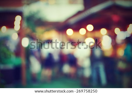 blurred crowd in market with bokeh lights, cross processing film style - stock photo