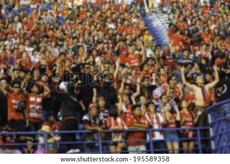 Blurred crowd of spectators on a stadium with a football match. - stock photo
