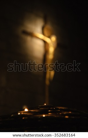 Blurred crucifix on stone wall and the candles at foreground. Symbolic contrast of light and darkness.  - stock photo